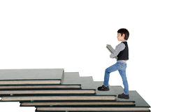 Little boy taking book go up book step Stock Images