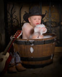 Little boy taking bubble bath. Little cowboy taking a bubble bath in whiskey barrel Stock Photos