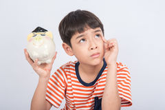 Little boy taking hammer thinking and trying to broke piggy bank Stock Photography