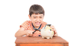 Little boy taking hammer trying to broke piggy bank on the table Royalty Free Stock Images