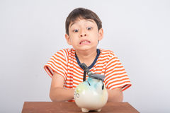 Little boy taking hammer trying to broke piggy bank on the table Stock Photo