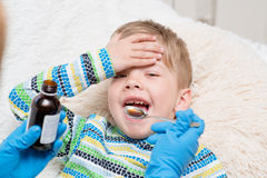 Little boy taking medicine with spoon. Royalty Free Stock Image
