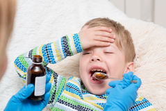 Little boy taking medicine with spoon Stock Photo