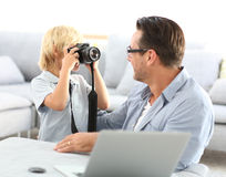 Little boy taking photos of his father Stock Images