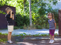 Little boy taking the picture of a litthe girl on sunny summer d Royalty Free Stock Photography