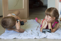 Little boy taking a picture of a little girl Stock Photos