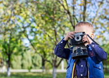 Little boy taking pictures in a park Stock Photos
