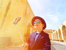 Little boy taking selfie stick picture while Royalty Free Stock Image