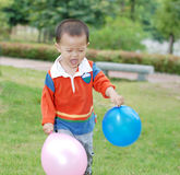 Little boy taking two balloons Royalty Free Stock Images