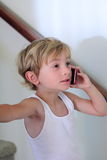 Little boy talking on the cell phone. A little blond boy engrossed on the cell phone wearing his undershirt.  Shallow depth of field Royalty Free Stock Photo