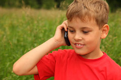 Little boy talking on cell phone outdoors Stock Images