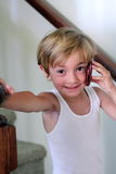 Little boy talking on the phone. A little blond boy talking on the cell phone wearing his undershirt.  Shallow depth of field Stock Photos