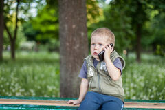 Little boy talking on the phone while sitting outdoors. Little boy talking on the phone, listening, sitting outdoors stock photo