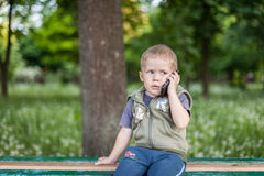 Little boy talking on the phone while sitting outdoors. Little boy talking on the phone, listening, sitting outdoors royalty free stock photos