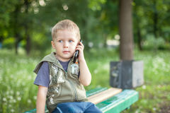 Little boy talking on the phone while sitting outdoors. Little boy talking on the phone, listening, sitting outdoors royalty free stock image