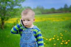 Little boy talking on the phone on a spring meadow Royalty Free Stock Photos