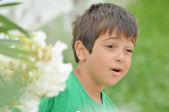 Little boy talking to somebody elses seriously. Little boy talking to somebody else`s seriously next to white oleander flowers Stock Image
