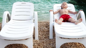Little boy tans on the sea coastline in white deck chair. Hight Definition Video : 29.97 FPS 14sec Please look another footages on my Train_Arrival Account stock video