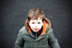 Little boy on the tarmac. Boy with puffer coat looking sad Royalty Free Stock Photo