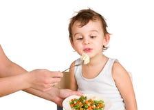 Little boy tasting vegetable salad Stock Images