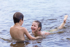 Little boy teaches his little sister to swim Stock Images