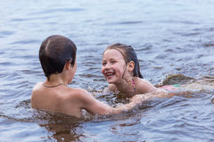 Little boy teaches his little sister to swim in a lake Stock Photos