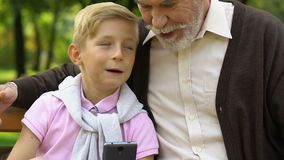 Little boy teaching his grandfather using smart phone to make a call, technology stock video footage