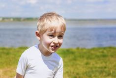 Little boy teasing and messing about, showing tongue and making. A face, against a blue sky outdoors, soft focus stock photography