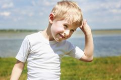 Little boy teasing and messing about, showing tongue and making. A face, against a blue sky outdoors, soft focus royalty free stock photography
