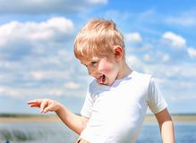 Little boy teasing and messing about, showing tongue and making. A face, against a blue sky outdoors, soft focus stock photo