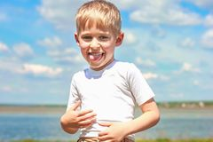 Little boy teasing and messing about, showing tongue and making. A face, against a blue sky outdoors, soft focus royalty free stock photo