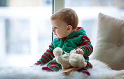 Little boy with teddy bear sits and looks out window. stock photo