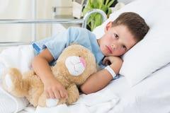 Little boy with teddy bear in hospital Stock Image