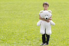 Little boy with teddy bear is looking at the camera. Outdoor, summer day. Copy space for text Royalty Free Stock Images