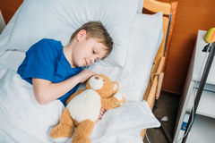Little boy with teddy bear lying in hospital bed royalty free stock images