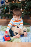 Little boy with a teddy bear and a machine at the Christmas tree Royalty Free Stock Images