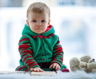 Little boy with teddy bear sits on background of window. royalty free stock images