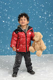 Little boy with teddy bear in the snow Stock Images