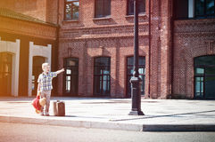 Little boy with teddy bear toy and suitcase shows forward Stock Images