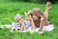 Little boy and teen age girl having picnic outdoors stock image