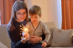 Little boy and teen girl holding a sparkler royalty free stock photography