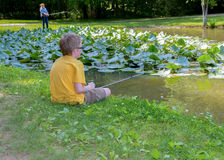 A little boy and a teenage girl fishing. In the summer time at a lake with lily pads and a teenage girl in the background.nAt Dan Nicholas Park in Rowan County Stock Photography