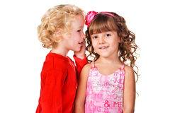 Little boy tell a secret to a little girl. Isolated over white Royalty Free Stock Photos