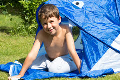 Little boy in a tent on a meadow. Little boy is playing on a meadow in a tent Royalty Free Stock Photos