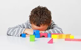Little boy testing his creativity by building towers with toy building blocks. Image of little boy testing his creativity by building towers with toy building royalty free stock photography