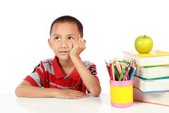 Little boy thinking. Something with many books around him Royalty Free Stock Image