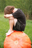 Little Boy Thinking. Little Boy Sitting and Thinking on Top of a Huge Pumpkin Royalty Free Stock Photography