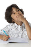 Little boy is thinking about his writing. On white background Royalty Free Stock Photography