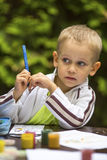 Little boy thinking with a pencil while drawing. Education. Royalty Free Stock Image