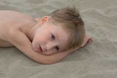 Little boy. Thougtful little boy lying on the sand Stock Photography